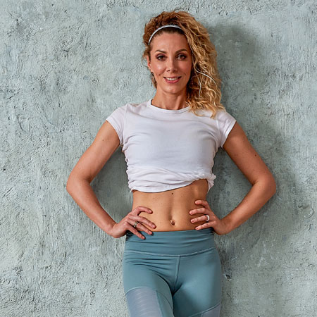 smiling-woman-after-workout-leaning-against-wall